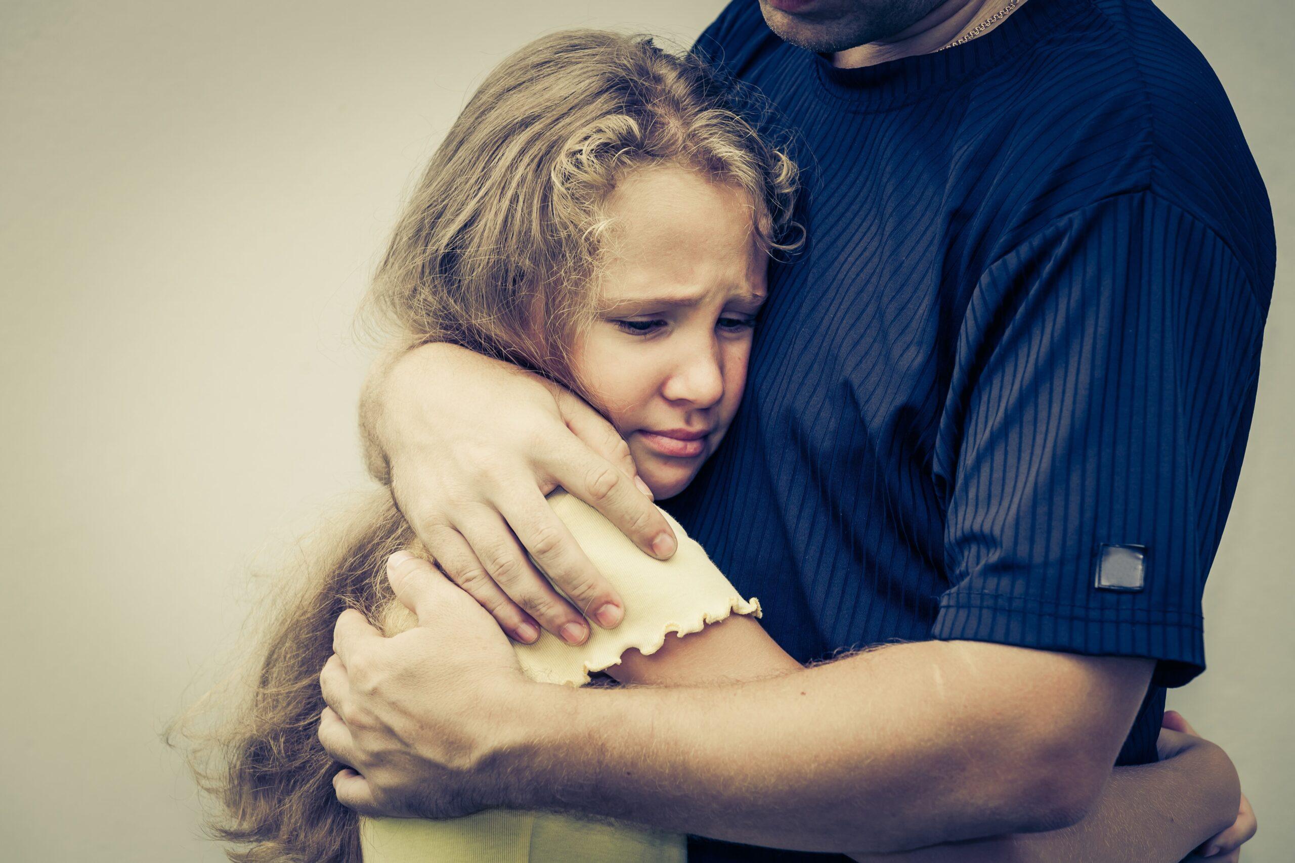 photo d'une enfant dans les bras d'un adulte, cherchant du soutien