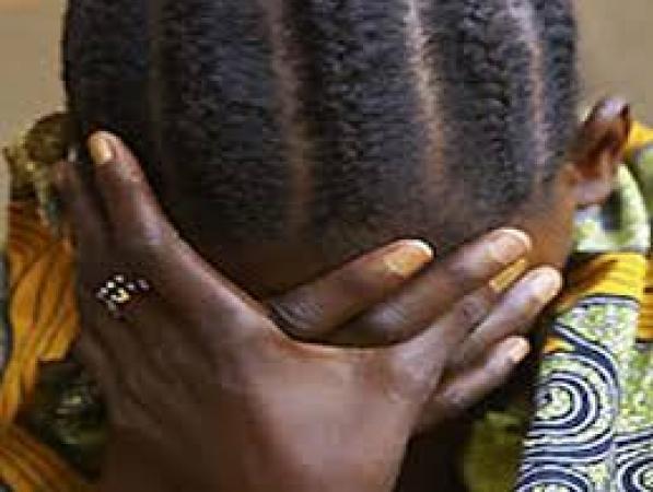 une enfant noire qui cache ses yeux pour pleurer