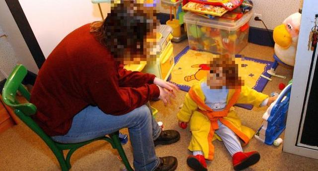 photo d'un baby sitter assis devant un petit enfant