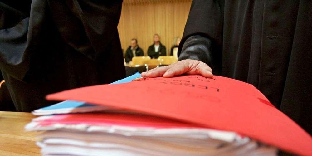photo d'un homme de loi la main sur un épais dossier dans une salle d'audience