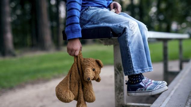 photo d'une peluche tenue tristement par un enfant seul sur un banc