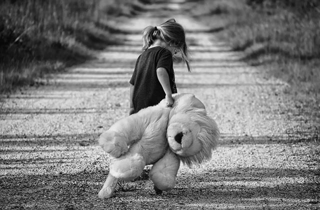 photo en noir et blanc d'une petite fille sur un chemin avec son gros nounours