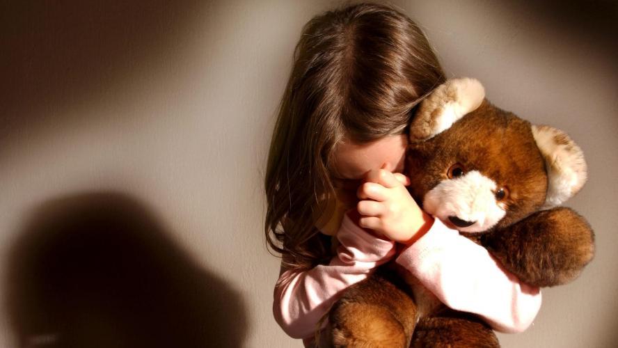 photo d'une petite fille en train de prier face a une presence floue