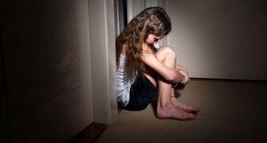 photo d'une enfant prostrée dans le couloir d'une maison