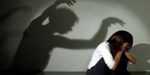 ombre menaçante d'un agresseur devant une enfant prostrée