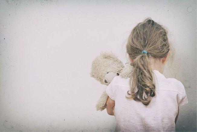 photo d'une fillette de dos avec son nounours