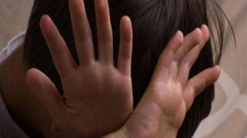 enfant les mains ouvertes croisées sur sa tête