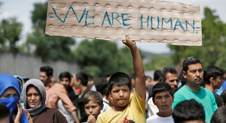 """enfant dans une foule de migrants levant haut une pancarte """"we are human"""""""