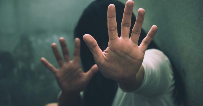 enfant dans une petite pièce avec les mains levées pour échapper aux coups
